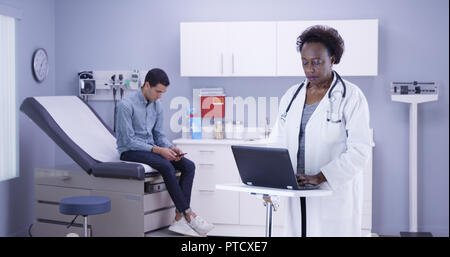 Senior black doctor taking notes of single latino patient on portable computer - Stock Photo