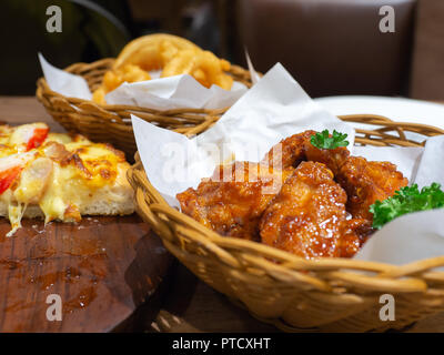 Deep fried chicken in a basket with parsley and seafood pizza topping with Crab, shrimp and ham On a wooden tray and Onion Rings in a basket - Stock Photo