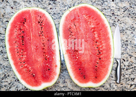 Closeup table lay flat top view of two halfs, halves of red watermelon cut in half with seeds, knife on kitchen granite countertop - Stock Photo