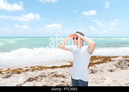 Young man in sunglasses standing on sand, sandy beach in Miami, Florida by ocean, sea water, waves on sunny day with blue sky, seaweed, two hands hold - Stock Photo