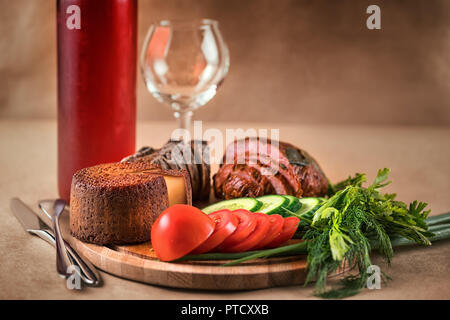 Still life with food and drink. Ham, cheese, vegetables and red wine on craft background - Stock Photo