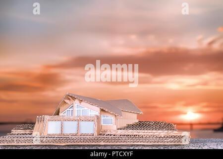 Luxury cottage cardboard model against bright sunset sky - Stock Photo