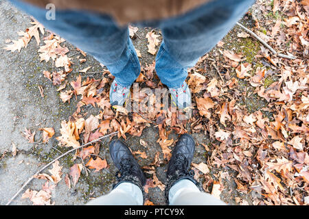 Shoes, fallen autumn brown orange many leaves on ground with woman man two couple feet flat lay top view down in Virginia suburbs hike trail road - Stock Photo