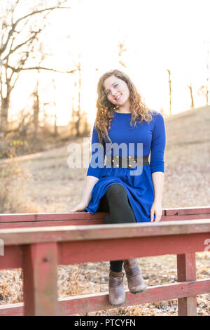 Young woman sitting in nature on top of wooden red painted small bridge over creek, river during sunset, sunrise in autumn, winter with backlight, bac - Stock Photo