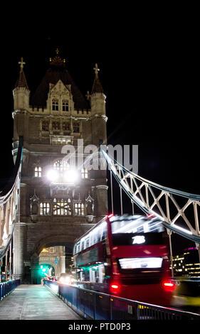 Driving double-decker bus on Tower Bridge, night view, London, England - Stock Photo