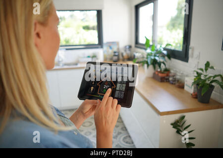 Woman at home using smart screen, automation domestic system - Stock Photo