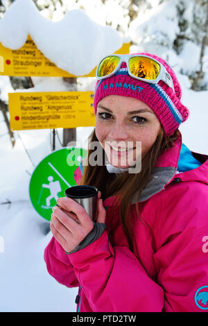 Woman in winter with tea, snowshoe tour to the Fellhorn, Reit im Winkl, Bavaria, Upper Bavaria, Germany - Stock Photo