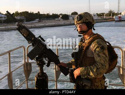 KEY WEST, Fla. (July 11, 2017) Gunner's Mate 2nd Class Julius Stastny, assigned to Coastal Riverine Group One, Detachment Guam, stands guard with a M240 machine gun aboard the expeditionary fast transport vessel USNS Spearhead (T-EPF 1) as the ship departs for operations at sea.  SPS-EPF 17 is a U.S. Navy deployment, executed by U.S. Naval Forces Southern Command/U.S. 4th Fleet, focused on subject matter expert exchanges with partner nation militaries and security forces in Central and South America. - Stock Photo