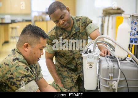 "Petty Officer 2nd Class John Lagmay (left) and Petty Officer 3rd Class Gabriel Adjetey (right), dental corpsmen with 4th Dental Battalion, 4th Marine Logistics Group, Marine Forces Reserve, set up dental equipment in preparation for Innovative Readiness Training Louisiana Care 2017 at East St. John High School in Reserve, La., July 11, 2017. The Louisiana Care Innovative Readiness Training event is a joint-service medical mission that provides the military with ""hands-on"" readiness training opportunities, while at the same time providing direct and lasting benefits to the residents of Louisian - Stock Photo"
