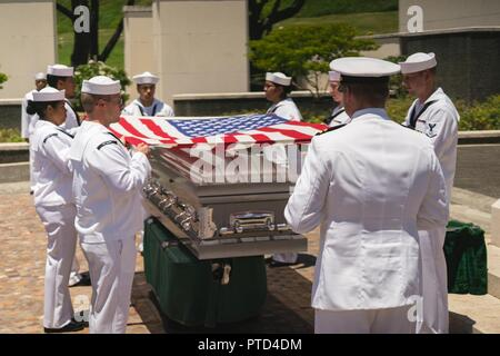 U.S. Navy Sailors drape the American flag over the casket. of U.S. Navy Seaman 1st Class Paul S. Raimond, of Converse, Louisiana, was laid to rest July 11, 2017 in the National Memorial Cemetery of the Pacific, in Honolulu, Hawaii. On Dec. 7, 1941, Raimond was assigned to the USS Oklahoma (BB-37), which was moored at Ford Island, Pearl Harbor, when the ship was attacked by Japanese aircraft. The attack on the ship resulted in the deaths of 429 crewmen, including Raimond. Raimond was recently identified through DNA analysis and returned to his family for burial with full military honors. - Stock Photo