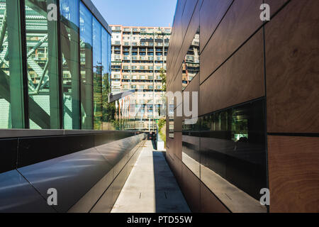 Longueuil, QC, Canada - 24-09-2018 - Contrast between new building with mirrors and old building in renovation. Mirrors reflecting other buildings at  - Stock Photo