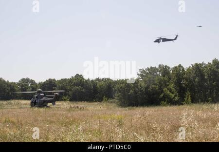 An AS532 Cougar helicopter from the Bulgarian Air Force picks up servicemembers during a combat search and rescue training in Plovdiv, Bulgaria, on July 11 during exercise Saber Guardian 17. A UH-60 Black Hawk helicopter from A Company, 2-10 Assault Helicopter Battalion, and a Mi-24 Hind helicopter from the Bulgarian Air Force circle for security. - Stock Photo