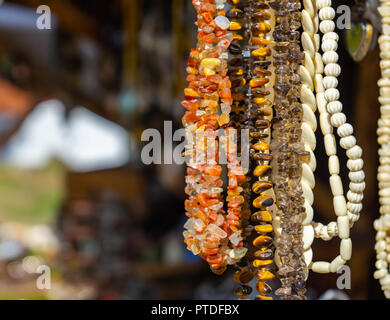 Hanging jewellery necklaces with coloured semi-precious stones, coloured stones and small white ivory pieces and amber. - Stock Photo