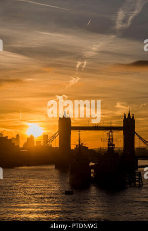 London, UK. 9th Oct 2018. The sun rises ofer Tower Bridge and HMS Belfast as people commute into work over London Bridge. Credit: Guy Bell/Alamy Live News - Stock Photo