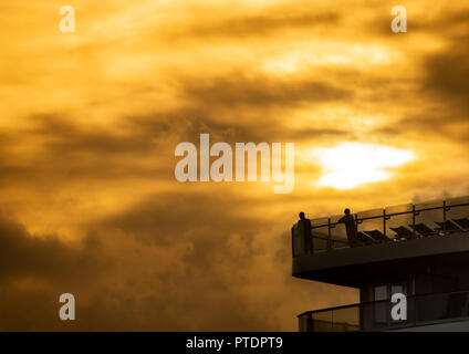 Passengers look out from th top deck of Cunard Line`s Queen Elizabeth cruise ship at sunrise. - Stock Photo