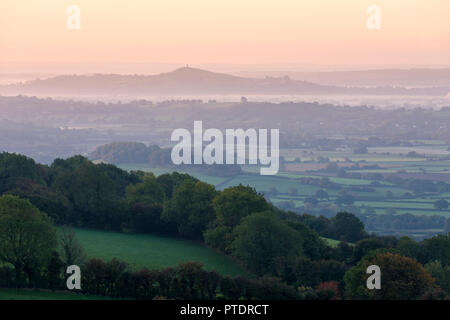 Early morning mist over the Somerset Levels and Glastonbury Tor viewed from Draycott Sleights in the Mendip Hills, Somerset, England. - Stock Photo