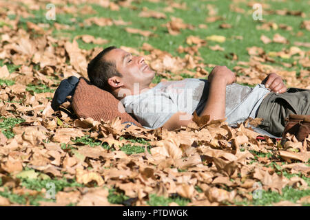 London UK. 9th October 2018. A man catching a nap in the afternoon sunshine on the park grass covered with autumn leaves  in Saint James's Park Credit: amer ghazzal/Alamy Live News - Stock Photo