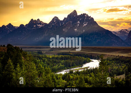 A summer sunset at the famed Snake River Overlook in Grand Teton National Park. The vista became iconic thanks to Ansel Adams' photo. - Stock Photo