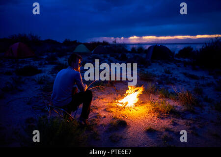 Man looking at campfire and tent at night on the lake beach - Stock Photo
