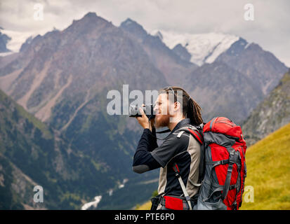 Man photographer with big backpack and camera taking photo of the mountains. Travel Lifestyle concept adventure active vacations outdoor - Stock Photo