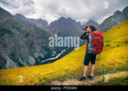 Man photographer with big backpack and camera taking photo in the mountains. Travel Lifestyle concept adventure active vacations outdoor - Stock Photo