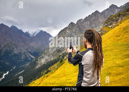 Man with dreadlocks taking photo with his phone in the mountains. Travel Lifestyle concept adventure active vacations outdoor - Stock Photo