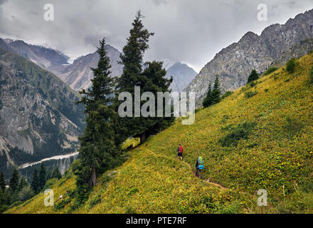 Two tourists with backpacks walking on the trail in the mountain valley at overcast sky background. Travel adventure concept - Stock Photo