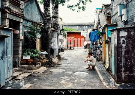 Beijing / China - JUN 24 2011: man waiting outside of his home in a typical city hutong