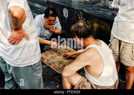 Beijing / China - JUN 24 2011: people playing typical xiangqi chinese chess on the street in a traditional chinese city hutong