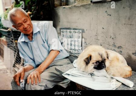 Beijing / China - JUN 24 2011: two man playing with a dog outside their home in a traditional chinese city hutong