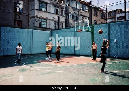 Beijing / China - JUN 24 2011: people playing basketball on the open street field in a residential area