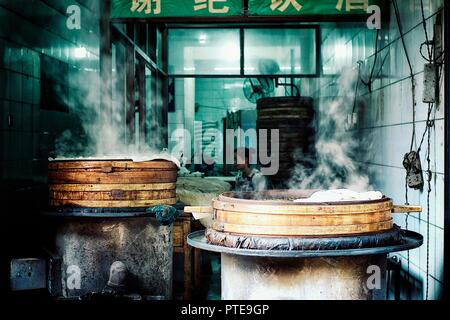 Xi'an / China - JUN 24 2011: young chinese woman preparing dumplings at a small street eatery restaurant - Stock Photo