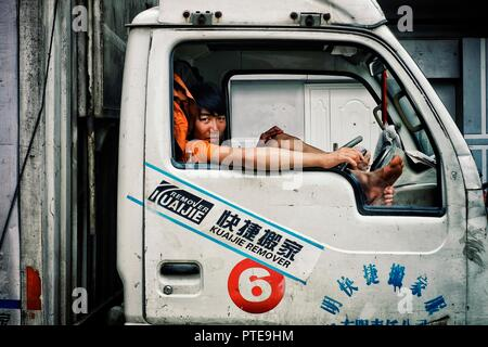 Beijing / China - JUN 24 2011: young boy waiting in the cabin of a lorry