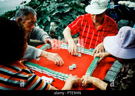 Beijing / China - JUN 24 2011: elderly people playing mahjong and cards in a park outdoor