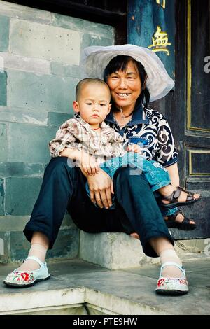 Beijing / China - JUN 24 2011: young mother with her kid in front of the gates of a temple - Stock Photo