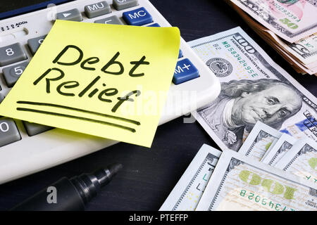 Debt relief handwritten on a note pad. - Stock Photo