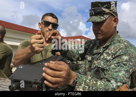 U.S. Marine Lance Cpl. Andrei B. Greenfield, left, breaks down a weapon with Philippine Marine Sgt. Rolly R. Cariaga, right, an AAV gunner with Assault Armor Battalion, aboard Camp Schwab, Okinawa, Japan, on July 18, 2017. The Philippine Marine Corps recently purchased AAVS and are working with U.S. Marines to learn different amphibious procedures – such as hand signaling, egress training, and water operations. This is the first time the Philippine military has trained on an American base. Greenfield, a Cohasset, Massachusetts native is an Amphibious Assault Vehicle crewman with Combat Assault - Stock Photo