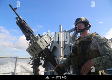 ULFPORT, Miss. (July 18, 2017) U.S. Navy Gunner's Mate 2nd Class Julius Stastny, assigned to Coastal Riverine Group one Detachment Guam, stands watch with a M240 machine gun aboard the expeditionary fast transport vessel USNS Spearhead (T-EPF 1), as the ship departs Gulfport, in support of Southern Partnership Station 17. SPS-EPF 17 is a U.S. Navy deployment, executed by U.S. Naval Forces Southern Command/U.S. 4th Fleet, focused on subject matter expert exchanges with partner nation militaries and security forces in Central and South America. - Stock Photo