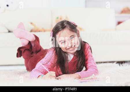 close up.little girl draws lying on the floor in the room - Stock Photo