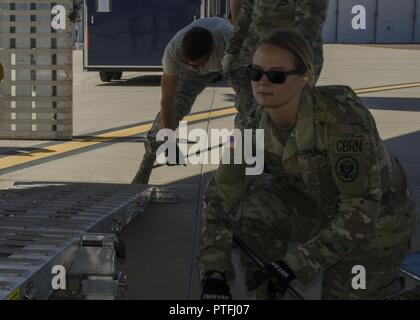 Army Sgt. Grace Ogesen, a survey team member with the Arizona National Guard's 91st Civil Support Team, sets up a ramp used to load vehicles onto a C-17 Globemaster cargo aircraft at Goldwater Air National Guard Base July 18. The 91st traveled to Buckley Air Force Base to participate in a multi-CST exercise to train together in one location for a large or widespread incident. (Ariz. Army National Guard - Stock Photo
