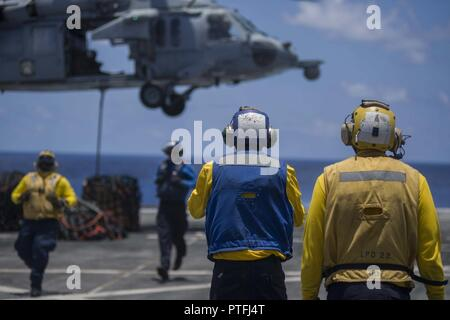 (July 19, 2017) Aviation Boatswain's Mate (Handling) Seaman Anthony Similton (center), a native of Augusta, Georgia, assigned to the Air department aboard the amphibious transport dock ship USS San Diego (LPD 22) signals personnel to return from hooking the cargo pendent on an MH-60S Sea Hawk, assigned to the Helicopter Sea Combat Squadron 23, during a vertical replenishment on the ship's flight deck. San Diego is embarked on a scheduled deployment as part of the America Amphibious Ready Group, which is comprised of more than 1,800 Sailors and 2,600 Marines assigned to the amphibious assault s - Stock Photo