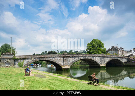 25 May 2018: Totnes, Devon, UK - Totnes Bridge and the River Dart with a man fishing and beautiful sky. The bridge was built in 1828. - Stock Photo
