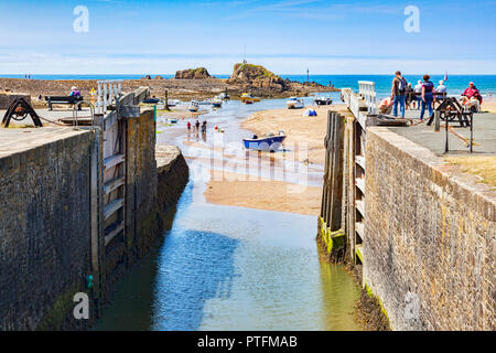 6 July 2018: Bude, Cornwall, UK - The canal and lock gates standing open to the sea, as people relax in the continuing heatwave. - Stock Photo