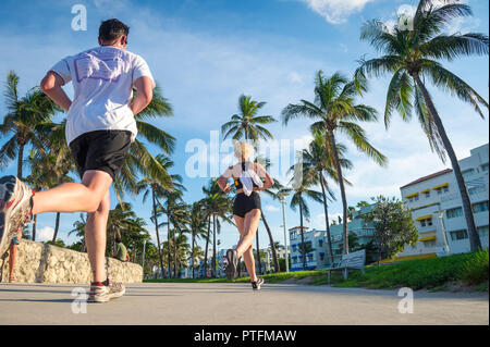 MIAMI - CIRCA AUGUST, 2018: A young man and woman run together against the Art Deco skyline of Ocean Drive in South Beach. - Stock Photo