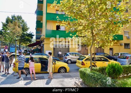 a family next to a yellow taxi in central tirana albania - Stock Photo