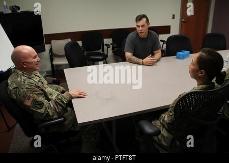 Chaplain (Maj.) David Ditolla talks with Pfc. James Ramsey and Maj. Fe Nall during one of the counseling sessions for the Moral Injury Program of the Intensive Outpatient Program. The programs are provided by the Department of Behavioral Health at Reynolds Army Health Clinic on Fort Sill, Okl - Stock Photo