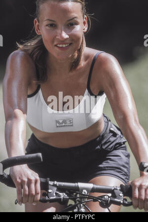 Sportliche junge Frau unterwegs mit dem Fahrrad, Sporty young woman traveling with a bicycle, Active, Activity, Adult, Bicycle, Bike, Caucasian, Count - Stock Photo