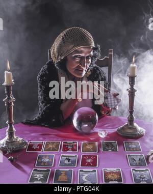 Wahrsagerin schaut in eine Kristallkugel und legt die Karten, Fortune teller looking into a crystal ball and puts the cards, Esotericism, Happiness, N - Stock Photo