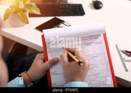 Man is filling form with pen. Picture of OMR sheet on the clipboard. - Stock Photo