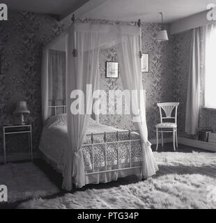 1960s, four poster, single metal bed in bedroom with individual luxury woollen shag-pile rugs on wooden floor, England, UK. - Stock Photo